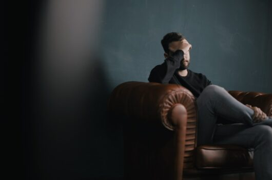 Stressed man sitting on couch